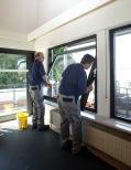 Zwei Mitarbeiter bauen die neuen Fenster ein.