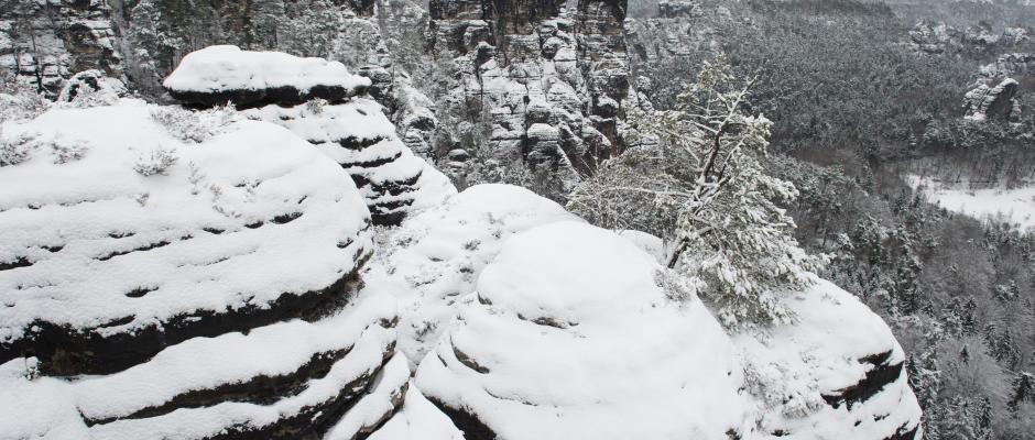 Schnee bedeckt sind in der Sächsischen Schweiz die Sandsteinfelsen. Foto: Sebastian Kahnert/Archiv