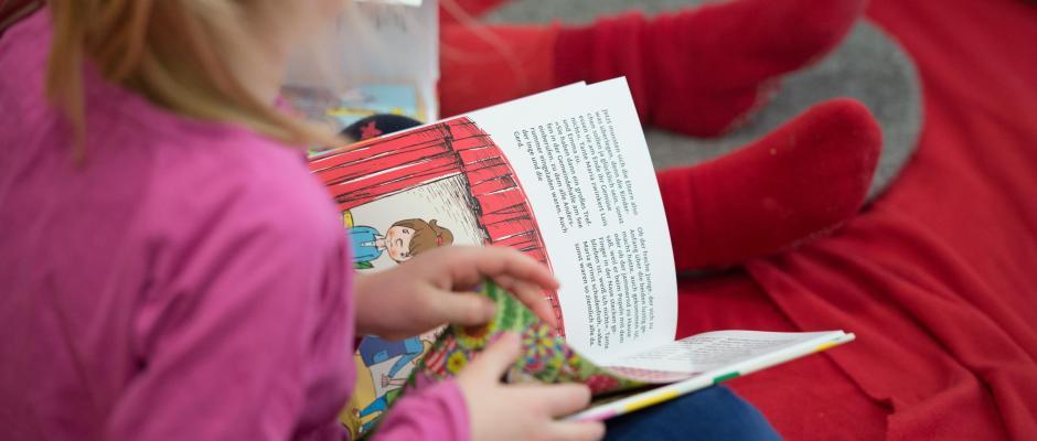 Ein Mädchen liest in einem Buch. Foto: Daniel Reinhardt/Archiv