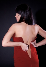 Portrait from back of overweighted woman trying to put on dress. Foto: Fotolia