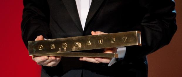 Samuel Finzi hält den Theaterpreis «Der Faust» in den Händen. Foto: Bernd Thissen/Archiv