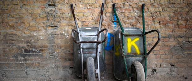 Zwei Schubkarren stehen an einer Wand. Foto: Arno Burgi/Archiv