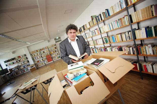 Jürgen Küfner (51), Direktor der Volkshochschule Dresden, zeigt einige der 13.000 geschenkten Bücher. Foto: Amac Garbe